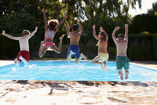 Kids Outdoor Swimming Pool  Rear View Children Jumping Into Outdoor Swimming Pool
